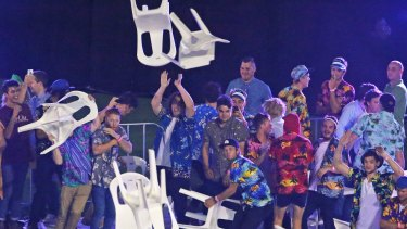 Spectators throw plastic chairs.