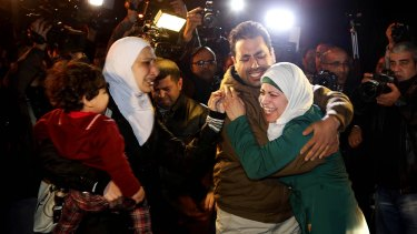 A man comforts the wife of captured Jordanian pilot Muath al-Kasaesbeh.