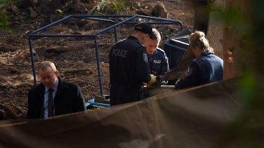 Police sift through soil at the crime scene.