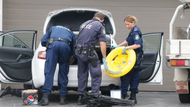 Police scour through cars at a Merrylands house in 2015 as part of a FPO search.