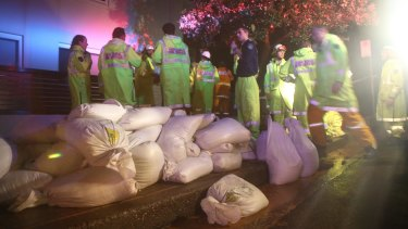 Emergency services survey the damage to homes on Collaroy Plateau and prepare sandbags for the rising King tides.
