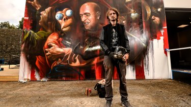Matt ''Adnate'' in front of his piece mocking the Banksy exhibition.