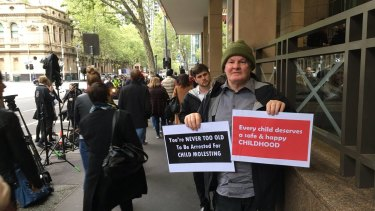 Brian Cherrie outside Melbourne Magistrates Court holding signs, ahead of Cardinal Pell's hearing.