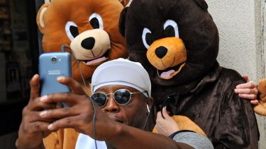 Thaddius Way takes a selfie with Rebecca, left, and Rachel Faullin, right, dressed as bears for The Stop the Florida Bear Hunt campaign protest in downtown Jacksonville.