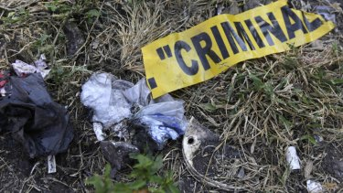 GRIM FIND: A part of a yellow police tape is seen at a garbage dump, where remains were found.