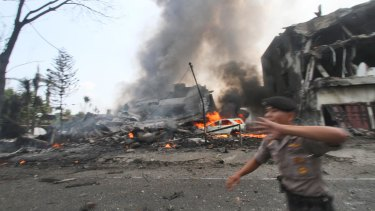 A police officer gestures at the crowd near the site where an Air Force cargo plane crashed in Medan.