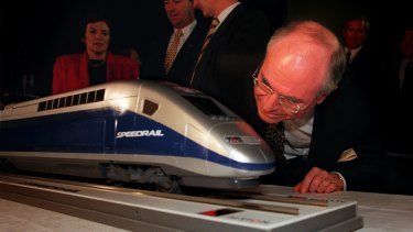 Former prime minister John Howard takes a close look at a model of a 'Speedrail', the winning tender for a proposed Sydney to Canberra service.