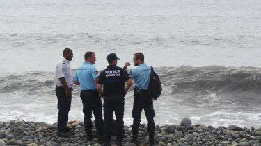 French gendarmes and police stand on the beach where a large piece of plane debris was found.