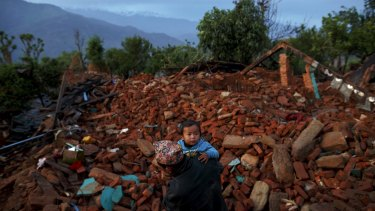 A local villager walks carrying a child amid debris at a devastated area in Gorkha, one of the worst hit regions.