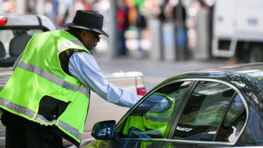 A parking inspector issues a ticket to a vehicle.