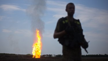Ending Western sanctions without losing influence in eastern Ukraine is one of Putin's goals, according to Dr Igor Sutyagin. Pictured: a Ukrainian serviceman stands guard, as flames erupt in the distance from a damaged gas pipeline in the Donetsk region.