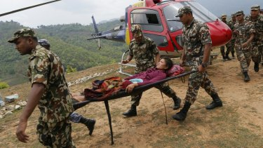 A woman suffering two broken legs from Saturday's massive earthquake, arrives by helicopter from the heavily-damaged Ranachour village.
