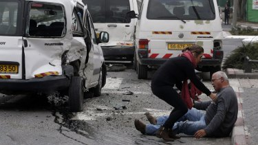 A wounded man sits on the street after a vehicle attack by a Palestinian motorist in Jerusalem in which a policeman was killed on November 5.