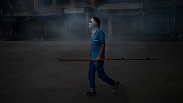 A Kashmiri protester stands in tear gas smoke during a protest in Srinagar.