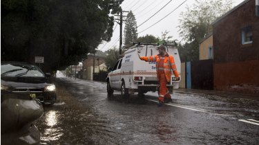 A State Emergency Service volunteer blocks off a flooded street in St Peters on June 5.