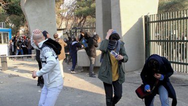 Students run away from stones thrown by police during a protest inside Tehran University.