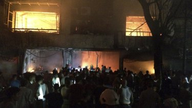 Iraqi firefighters and civilians gather at the site after a car bomb at a commercial area in Karada in Baghdad.