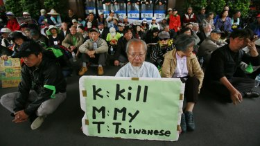 Protesters against Taiwan's trade pact with China stage a sit-in outside parliament with a sign denouncing the ruling Kuomintang in 2014.
