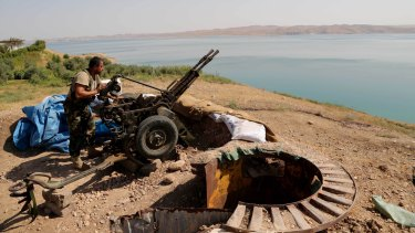 A Kurdish peshmerga fighter prepares his weapon at his combat position near the Mosul Dam.