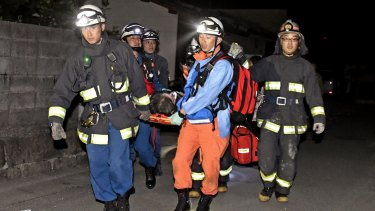 Firefighters carry an injured person after the earthquake, in the town of Mashiki.