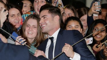 Zac Efron is caught in the crossfire of selfie sticks on the red carpet.