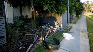 The remains of a fence that was hit by a car after a shooting.