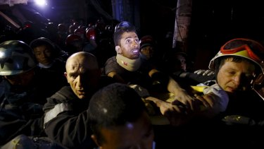 Rishi Khanal looks around at the surroundings as he is pulled from the rubble of a building after four days trapped.
