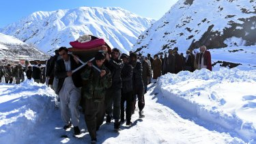 Afghan men carry a victim of the avalanches after funeral prayers.
