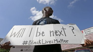 Niamke Ledbetter, of Oak Cliff, Texas, holds a sign at a Black Lives Matter protest in Dallas on Sunday.