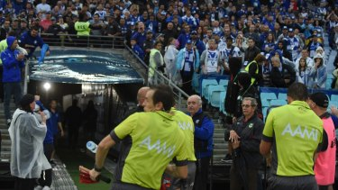 Dark day: a touch judge is hit by a water bottle after the South Sydney v Canterbury match.