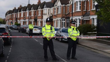 Police officers at the scene of the terror raid on London's Harlesden Road. Three more women have now been arrested in east  London.