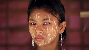 A Rohingya girl with her face covered in 'thanaka', a comestic paste from ground bark, stands in her family's tent in Kutupalong refugee camp in Bangladesh.