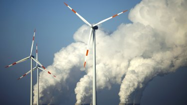 Steam billows from the cooling towers of brown coal power station behind wind turbines near Cottbus, eastern Germany