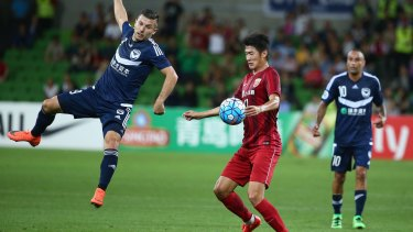 Kosta Barbarouses of Melbourne Victory is airborne as he challenges Hai Yu of Shanghai SIPG.