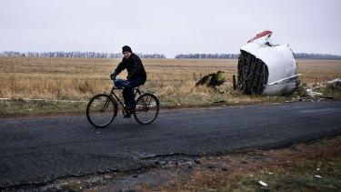 A man rides his bike past the MH17 crash site, 80 kilometres east of Donetsk.