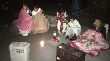 Residents wrap themselves in blankets on road in Mashiki.