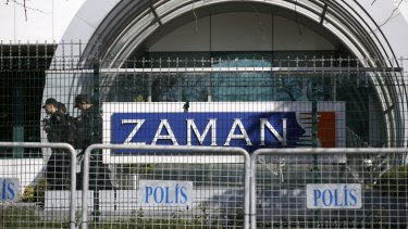 Riot police officers walk by the headquarters of <i>Zaman</i> newspaper in Istanbul after it was shut down.