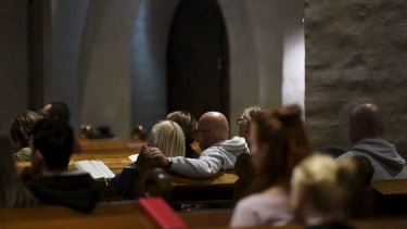 People attend a prayer service for stabbing victims at the Cathedral in Turku, Finland.