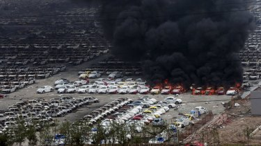 Smoke rises as damaged vehicles are seen burning near the site of Wednesday night's explosions.