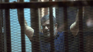 Sentenced to death: Ousted Egyptian President Mohammed Morsi raises his hands as he sits behind glass in a courtroom.
