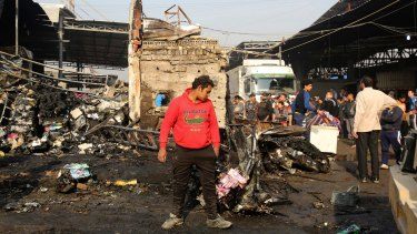 Citizens inspect the scene after a car bomb explosion at a crowded outdoor market in Sadr City.