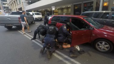A man is pulled from his vehicle on Bond Street on Thursday night.