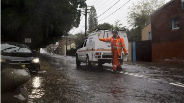 An SES worker blocked off Campbell Street in St Peters, Sydney, after a manhole cover was dislodged by the force of the water.