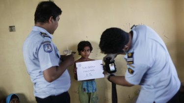 Indonesian immigration officials take photos of an ethnic Rohingya girl upon her arrival at a temporary shelter in Lapang.