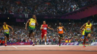 Silence please: Jamaica's Usain Bolt  crosses the finish line to win gold.