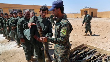 Syrian Internal Security Forces receive weapons during their graduation ceremony, at Ain Issa desert base, in Raqqa on Thursday. Some 250 residents of Raqqa are the latest batch to graduate from a brief US-training course.