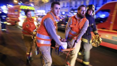 A woman is evacuated from the Bataclan theatre in Paris on Friday night after more than 100 people were killed in a terrorist attack. In total more than 150 people died in attacks across the French capital.