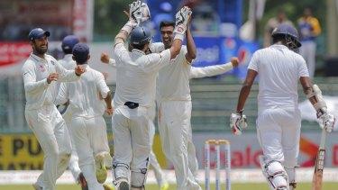 India's off-spinner Ravichandran Ashwin high-fives wicketkeeper Naman Ojha after dismissing Lahiru Thirimanne.