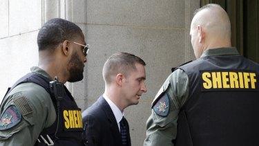 Officer Edward Nero, centre, one of six Baltimore city police officers charged in connection to the death of Freddie Gray, arrives at a courthouse to receive a verdict in his trial in Baltimore on Monday.