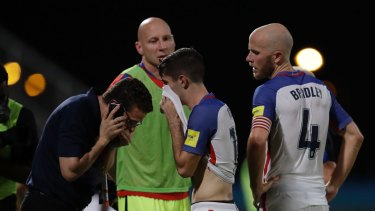 Christian Pulisic, centre, and Michael Bradley, walk off the pitch after the loss.